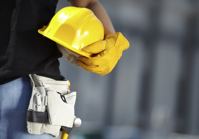 builder with yellow helmet and working gloves on building site