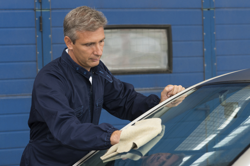 Mechanic Cleaning Windshield With A Cloth At Garage