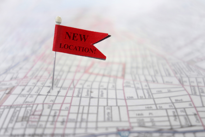 Closeup of a New Location pin flag on a map,