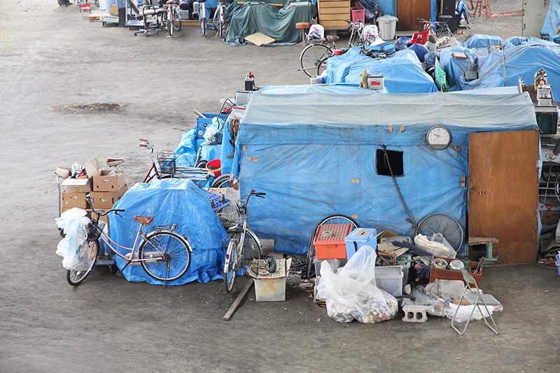 homeless encampment, tents, bicycles, junk, trash